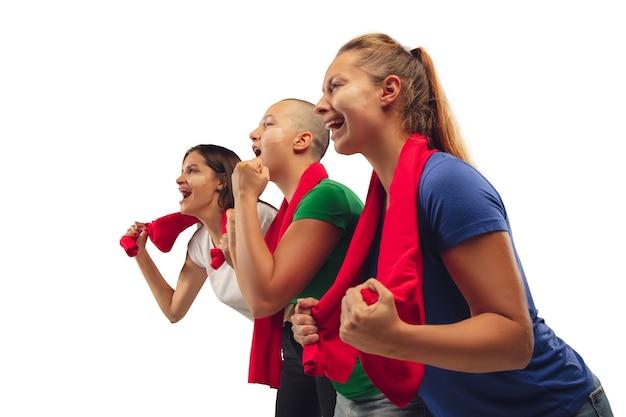 Mieć nadzieję. kobiece kibice piłki nożnej doping dla ulubionej drużyny z jasnymi emocjami na białym tle na tle białego studia. piękne kaukaskie kobiety wyglądają na podekscytowane, wspierające. pojęcie sportu, zabawy, wsparcia.