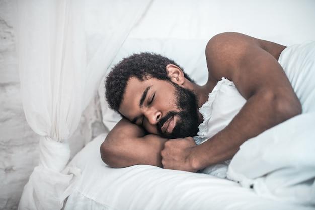 Mieć sen. młody dorosły brodaty afroamerykanin mocno śpi w białym łóżku w domu z ręką pod głową