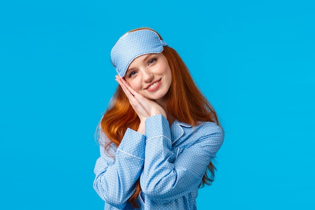 Mieć słodkie sny. czuła, urocza i kobieca ruda nastolatka gotowa spać mocno, ubrana w maskę do spania i piżamę, opierająca się na poduszkach jak poduszka, uśmiechnięta zadowolona i zrelaksowana, niebieska ściana