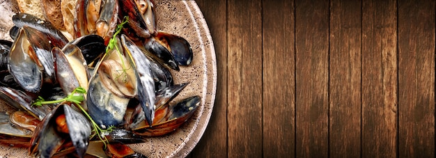 Mięczaki w kremowym sosie serowym z grzankami, na talerzu, na tle drewnianych z miejsca na kopię. poziomy