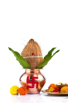 Miedź kalash z liśćmi kokosa i mango oraz pooja thali z diyą, kumkum i słodyczami z kwiatową dekoracją. niezbędny w hinduskiej pudży.