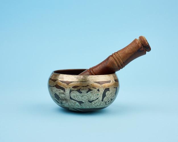 Miedziana misa śpiewająca i drewniany kij, tybetański instrument muzyczny