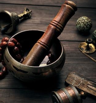 Miedziana miska do śpiewania i drewniany kij na brązowym stole