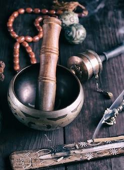 Miedziana miska do śpiewania i drewniany kij