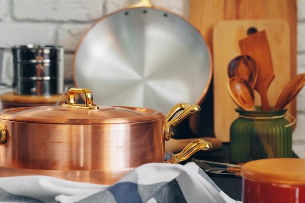 Miedziane naczynia kuchenne z drewnianymi naczyniami kuchennymi z bliska