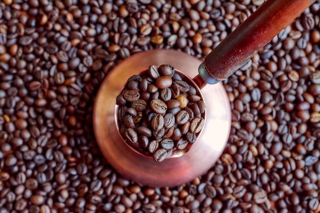 Miedziany cezve wypełniony ziarnami kawy.
