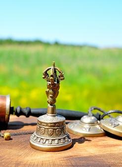 Miedziany dzwon z tybetańskimi przedmiotami religijnymi