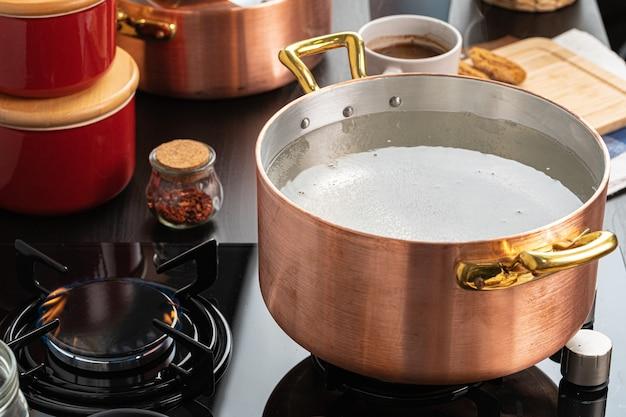 Miedziany garnek z wrzącą wodą na kuchence gazowej z bliska