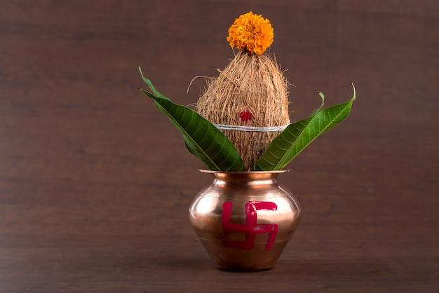 Miedziany kalash z liściem kokosa i mango z kwiatową dekoracją na drewnie.