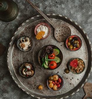 Miedziany talerz z wyborem marynowanych potraw.
