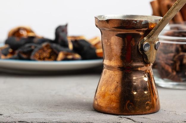 Miedziany turk z kawą i kawałkami suszonych owoców na stole