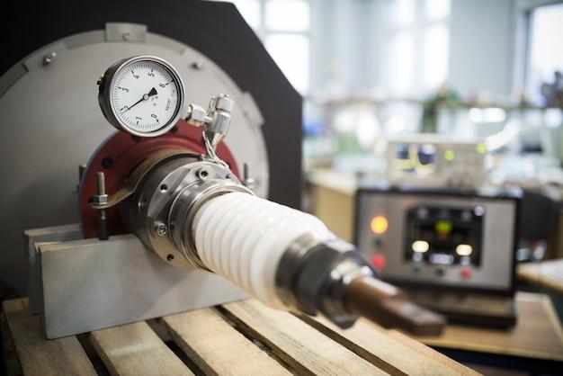 Miedziany zacisk do podłączenia kabla wysokiego napięcia w stalowym gnieździe na drewnianym stojaku