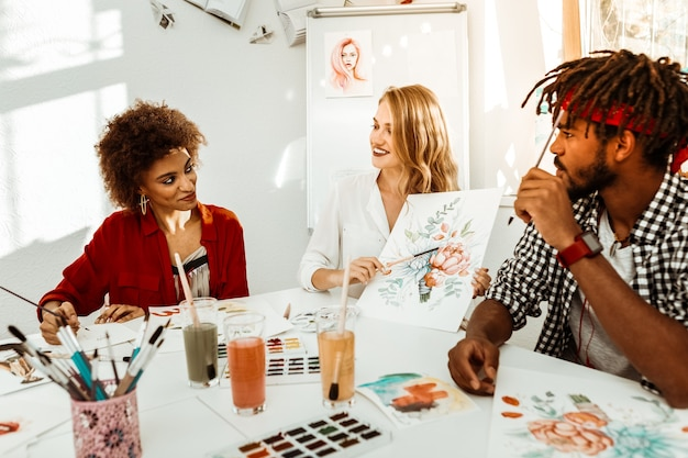 Między studentami. utalentowana blond nauczycielka plastyki siedzi między studentami i słucha jej