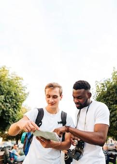 Międzykulturowi męscy przyjaciele patrzeje mapę