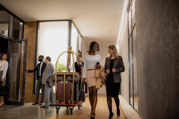 Międzykulturowi podróżujący służbowo komunikujący się w ruchu z portierem pchającym wózek z bagażami między nimi wewnątrz hotelu