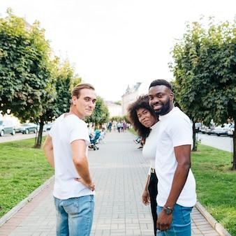 Międzykulturowi przyjaciele patrząc wstecz na aparat