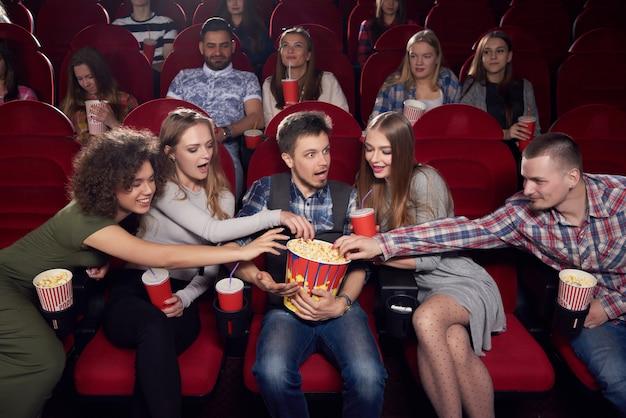 Międzynarodowa grupa kobiet i mężczyzn spędzających czas w kinie, wyciągających ręce po popcorn jednego zszokowanego chłopca w środku. chciwość, zły i zdziwiony mężczyzna trzymający duże wiadro z pysznym popcornem.