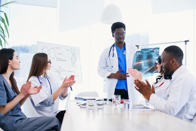 Międzynarodowa grupa profesjonalnych młodych lekarzy klaszcze w dłonie i uśmiecha się na konferencji medycznej w nowoczesnej klinice