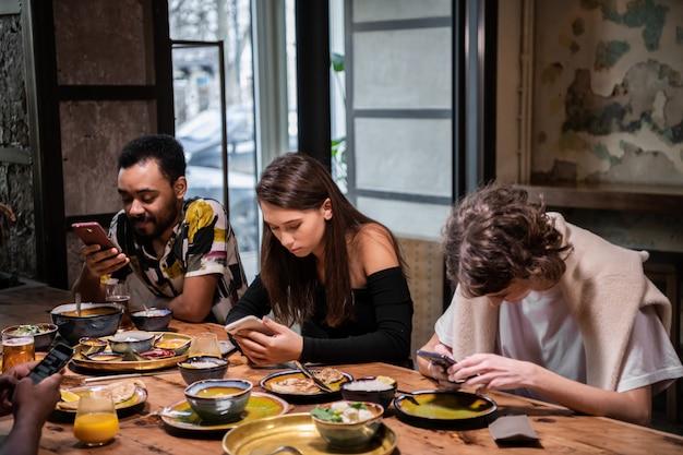 Międzynarodowa grupa studentów dzielących się jedzeniem w kawiarni i korzystających z bezpłatnego wi-fi
