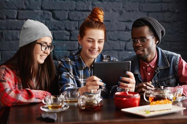 Międzynarodowa grupa trzech przyjaciół siedzących w kawiarni i oglądających filmy online na tablecie
