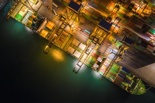 Międzynarodowa morska stacja towarowa ogromnymi ładunków kontenerami wysyła nad widok frome trutnia kamera przy nocą