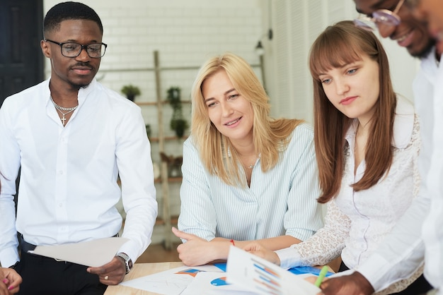 Międzynarodowa, pozytywna firma ludzi pracuje w biurze i przegląda dokumenty robocze.