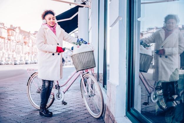Międzynarodowe piękno. pozytywnie zadowolony dziewczyna trzyma uchwyt, stojąc w pobliżu swojego roweru