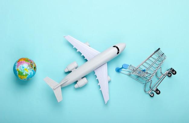 Międzynarodowe zakupy, dostawa lotnicza. globus, samolot, wózek supermarketu na niebieskim tle. widok z góry.