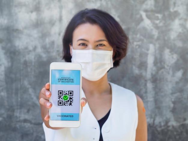 Międzynarodowe zaświadczenie o szczepieniu, inteligentny cyfrowy paszport z kodem qr na ekranie smartfona, pokazany przez zaszczepioną azjatkę, noszącą maskę na twarzy i pomarańczowy bandaż na ramieniu.