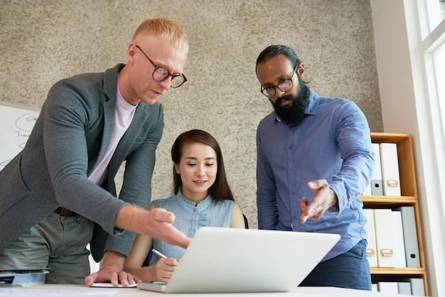 Międzynarodowi koledzy patrzeje laptopu ekran przy biurowym spotkaniem