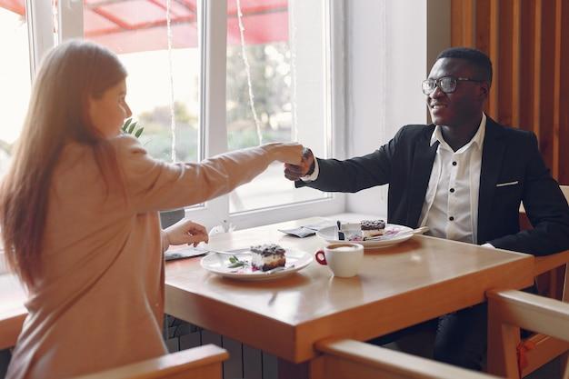 Międzynarodowi ludzie siedzą w kawiarni i piją kawę