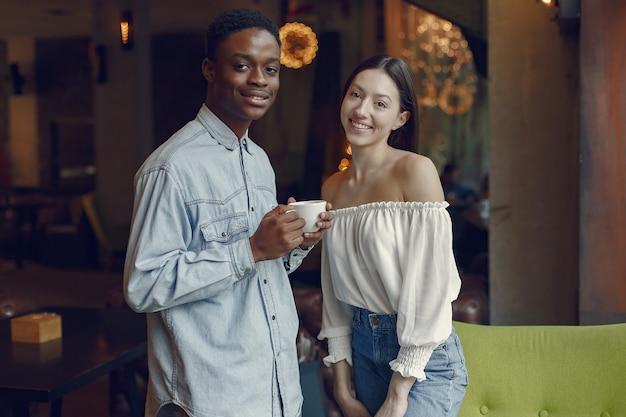 Międzynarodowi ludzie stojący w kawiarni i pijący kawę