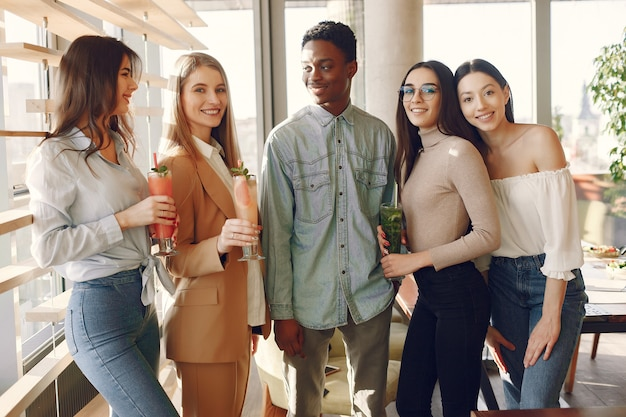 Międzynarodowi ludzie stojący w kawiarni i pijący koktajle