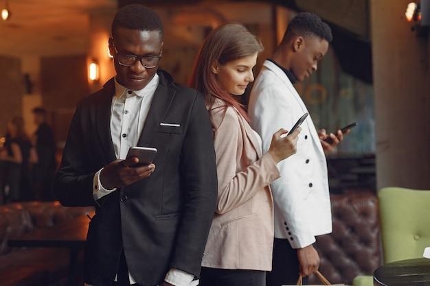 Międzynarodowi ludzie stojący w kawiarni z telefonem komórkowym