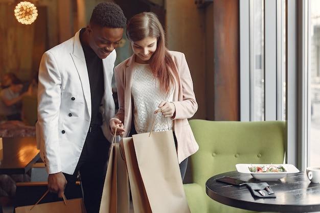 Międzynarodowi ludzie stojący w kawiarni z torbami na zakupy