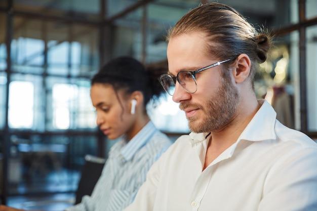Międzynarodowi poważni koledzy pracujący i używający słuchawek siedząc przy stole w biurze