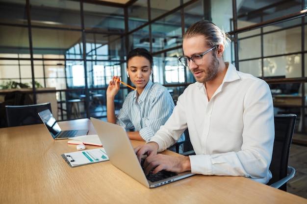 Międzynarodowi poważni koledzy pracujący z laptopami, siedząc przy stole w biurze