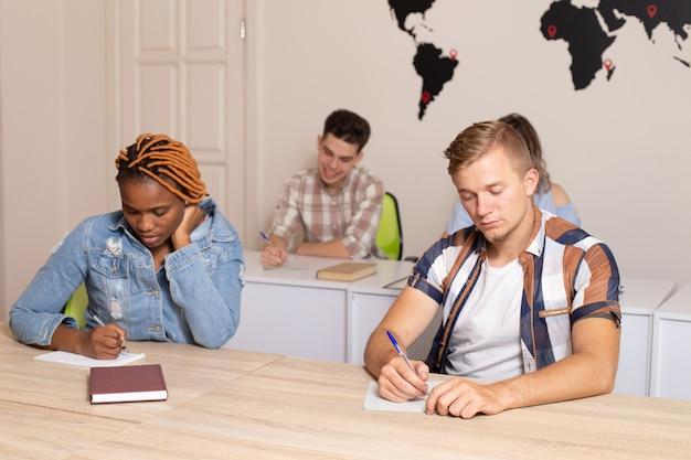Międzynarodowi ucznie w sala lekcyjnej z światową mapą na ścianie na tle
