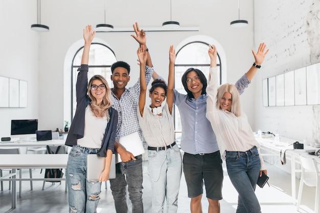 Międzynarodowi zmęczeni studenci świętujący zakończenie egzaminów i śmiejący się w sali wykładowej. szczęśliwi niezależni programiści wykonujący długi projekt i pozujący z uśmiechem, trzymając laptopy.