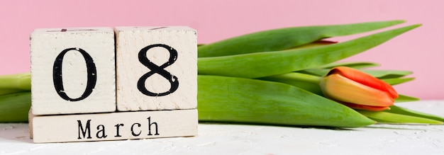 Międzynarodowy dzień kobiet. drewniany kalendarz 8 marca i czerwone tulipany na różowym tle, baner