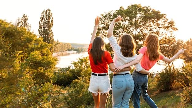 Międzynarodowy dzień kobiet. kobiety, kobieta, feminizm, przyjaciele, siła dziewczyny, różnorodność, koncepcja kobiecości. grupa trzech szczęśliwych młodych kobiet zabawy na świeżym powietrzu.