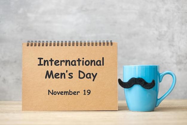 Międzynarodowy dzień mężczyzn z papierowym notatnikiem, niebieska filiżanka kawy lub kubek herbaty i wystrój czarne wąsy na stole. szczęśliwy dzień ojca i koncepcja uroczystości