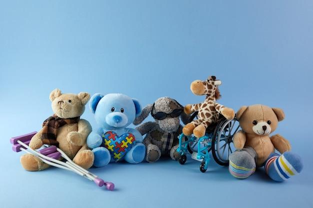 Międzynarodowy dzień osób niepełnosprawnych. wózek inwalidzki z zabawkami znak różnych niepełnosprawności na niebieskim tle.
