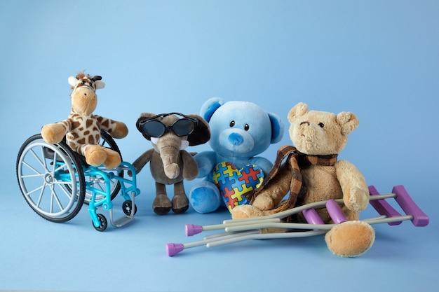 Międzynarodowy Dzień Osób Niepełnosprawnych. Wózek Inwalidzki Z Zabawkami Znak Różnych Niepełnosprawności Na Niebieskim Tle. Premium Zdjęcia