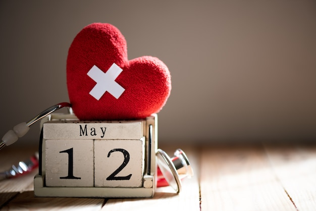 Międzynarodowy dzień pielęgniarek, 12 maja. czerwone serce z stetoskop na drewniane tła.