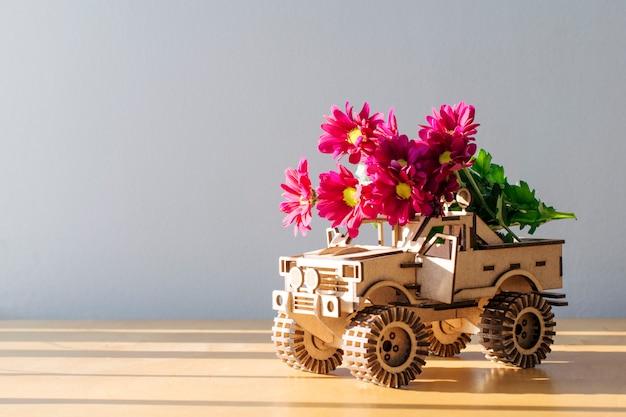 Międzynarodowy dzień szczęśliwych kobiet. drewniany samochód z kwiatami na lekkim tle z odbitkową przestrzenią