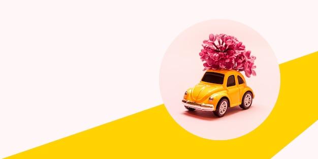Międzynarodowy dzień szczęśliwych kobiet. zabawkarski żółty samochód z lilą kwiat gałąź na różowym tle z miejscem dla teksta.