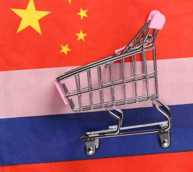 Międzynarodowy, globalny supermarket. mini wózek na zakupy na tle niewyraźnej flagi rosji i chin. koncepcja zakupów.