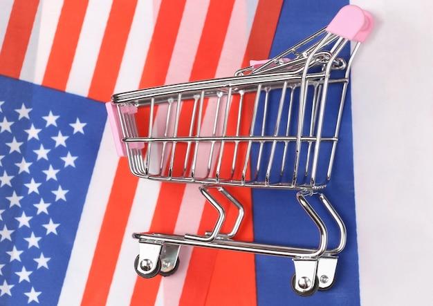 Międzynarodowy, globalny supermarket. mini wózek na zakupy na tle niewyraźnej flagi usa i rosji. koncepcja zakupów.