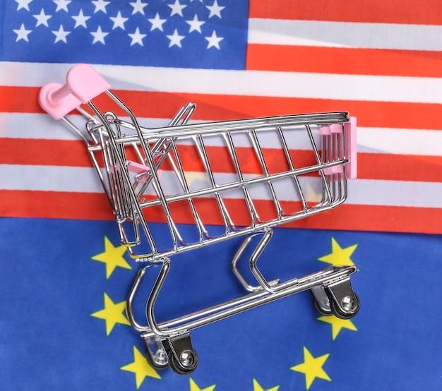 Międzynarodowy, globalny supermarket. mini wózek na zakupy na tle niewyraźnej flagi usa i unii euro. koncepcja zakupów.